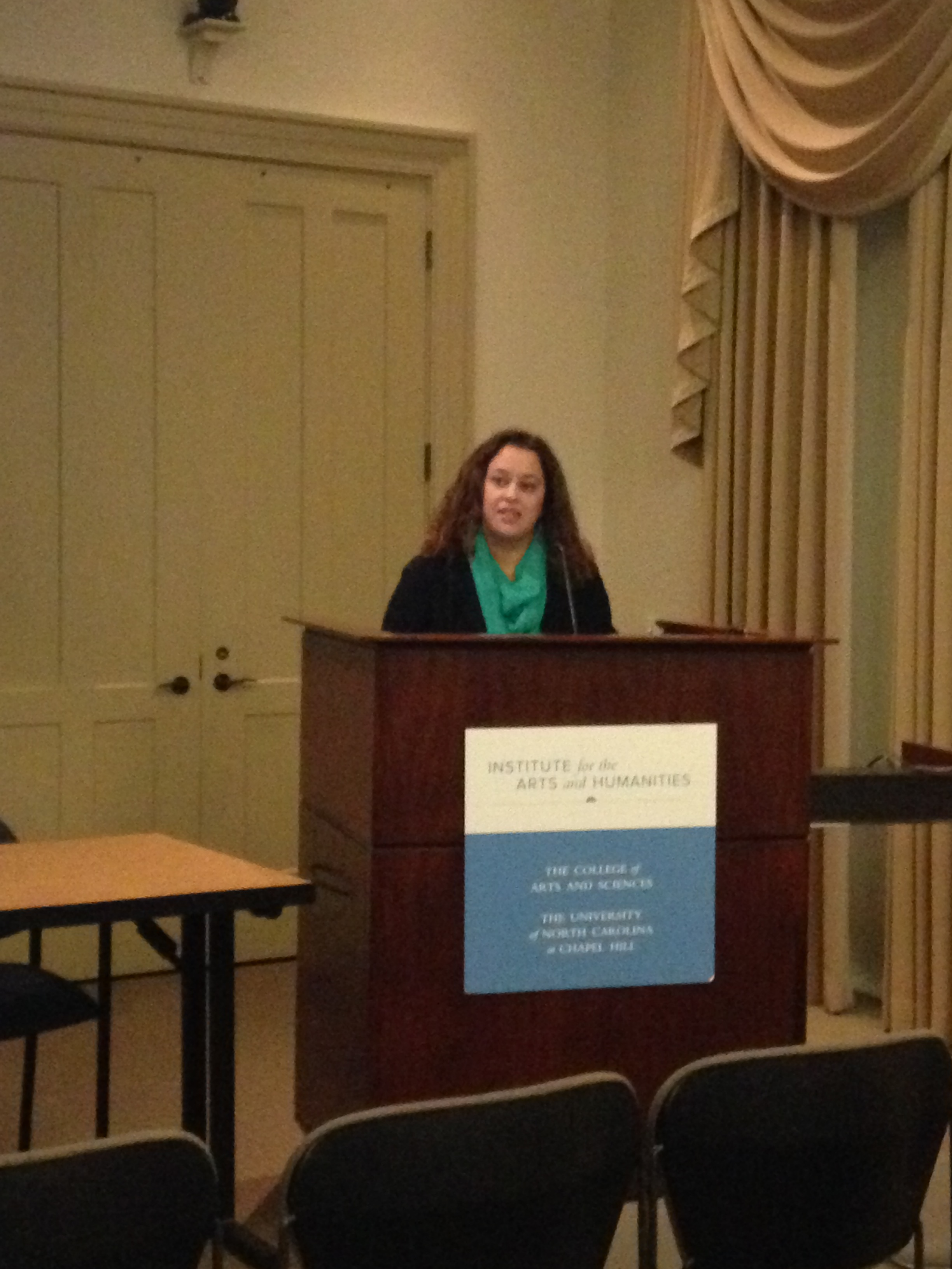 Dr. Christina Bejarano standing at a podium, looking out into the symposium crowd, and speaking into a microphone.