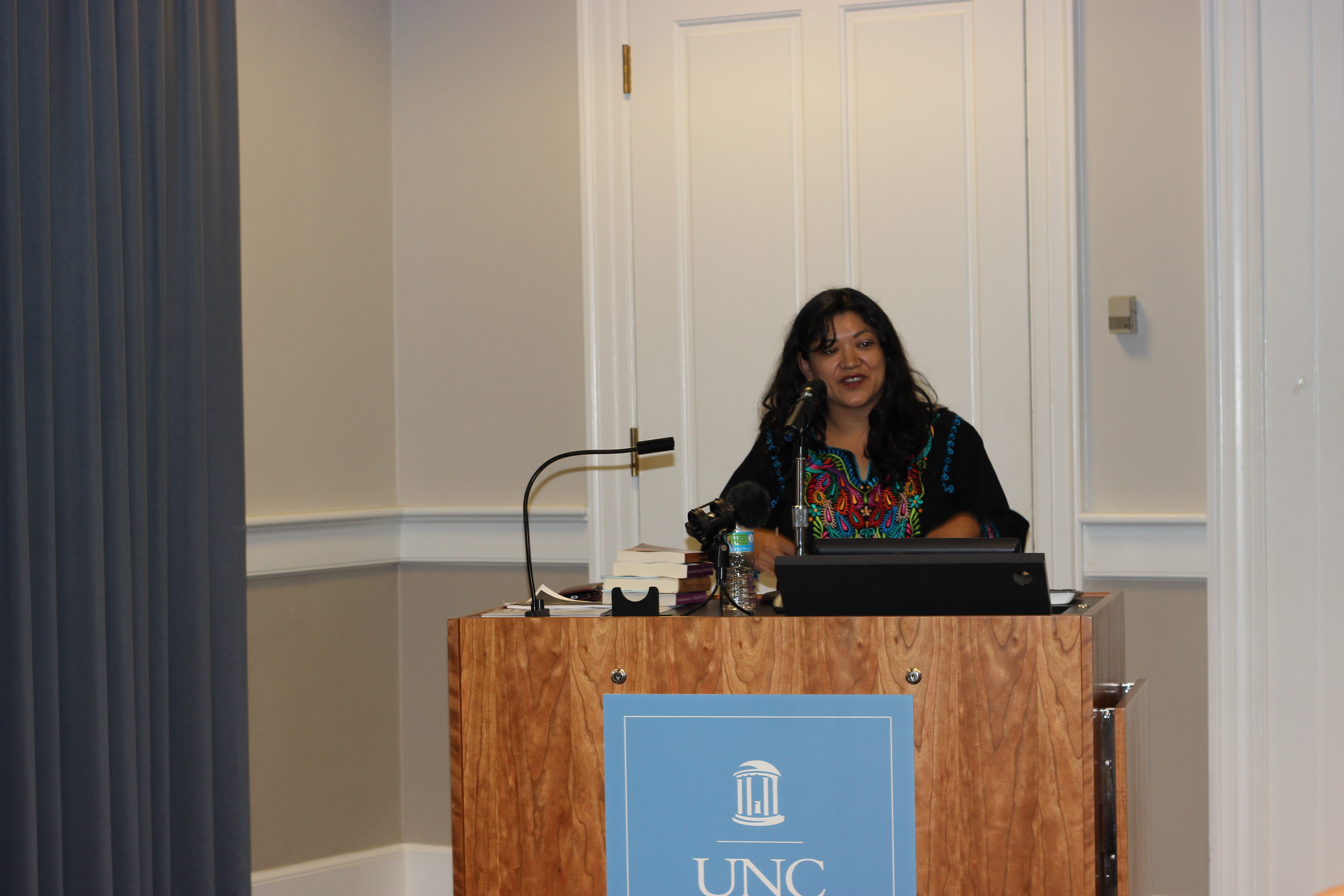 Reyna Grande standing at a podium and looking to her left as she speaks into a microphone.