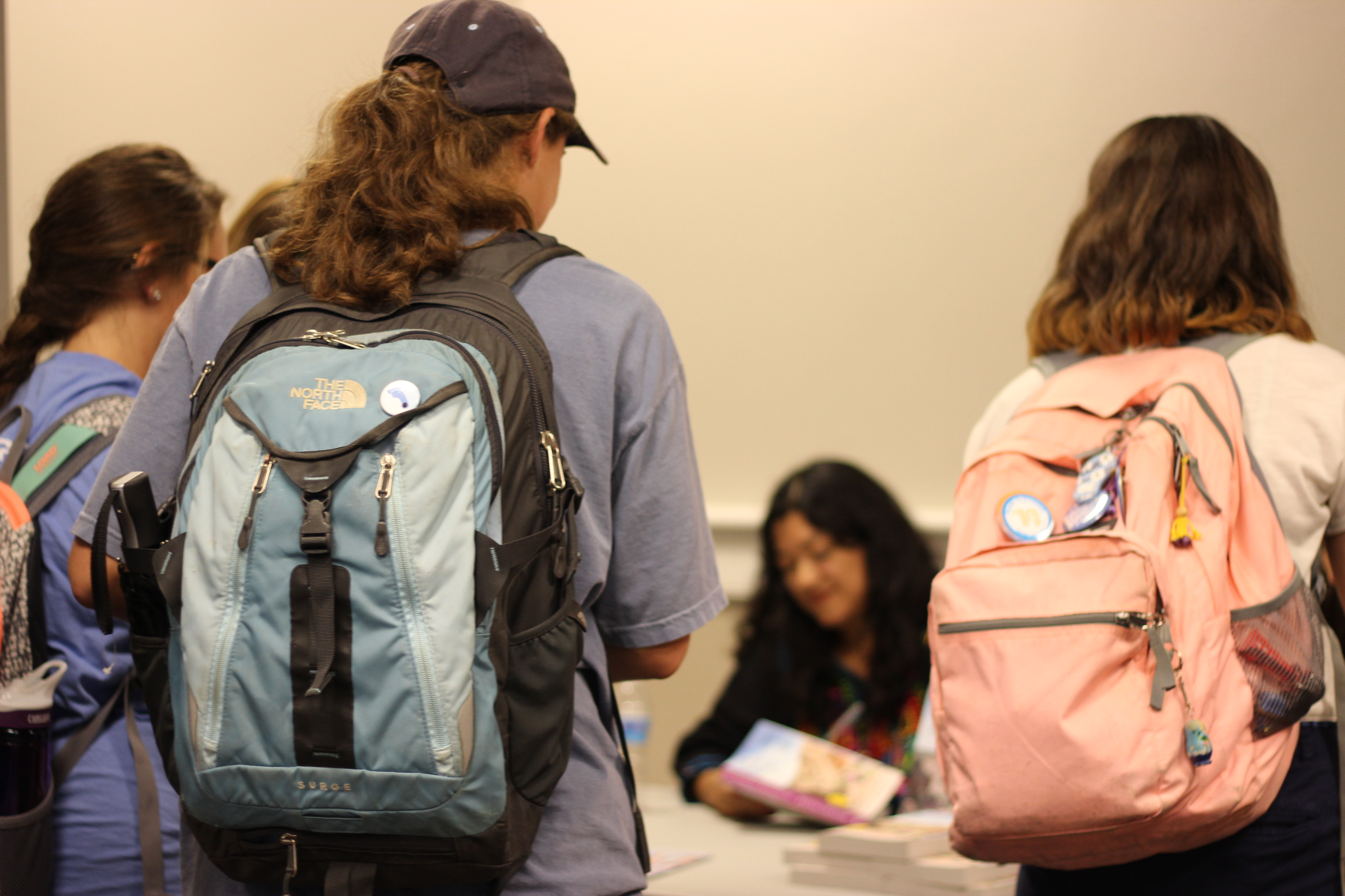The backs of three students facing Reyna Grande as she sits signing books at a large folding table.