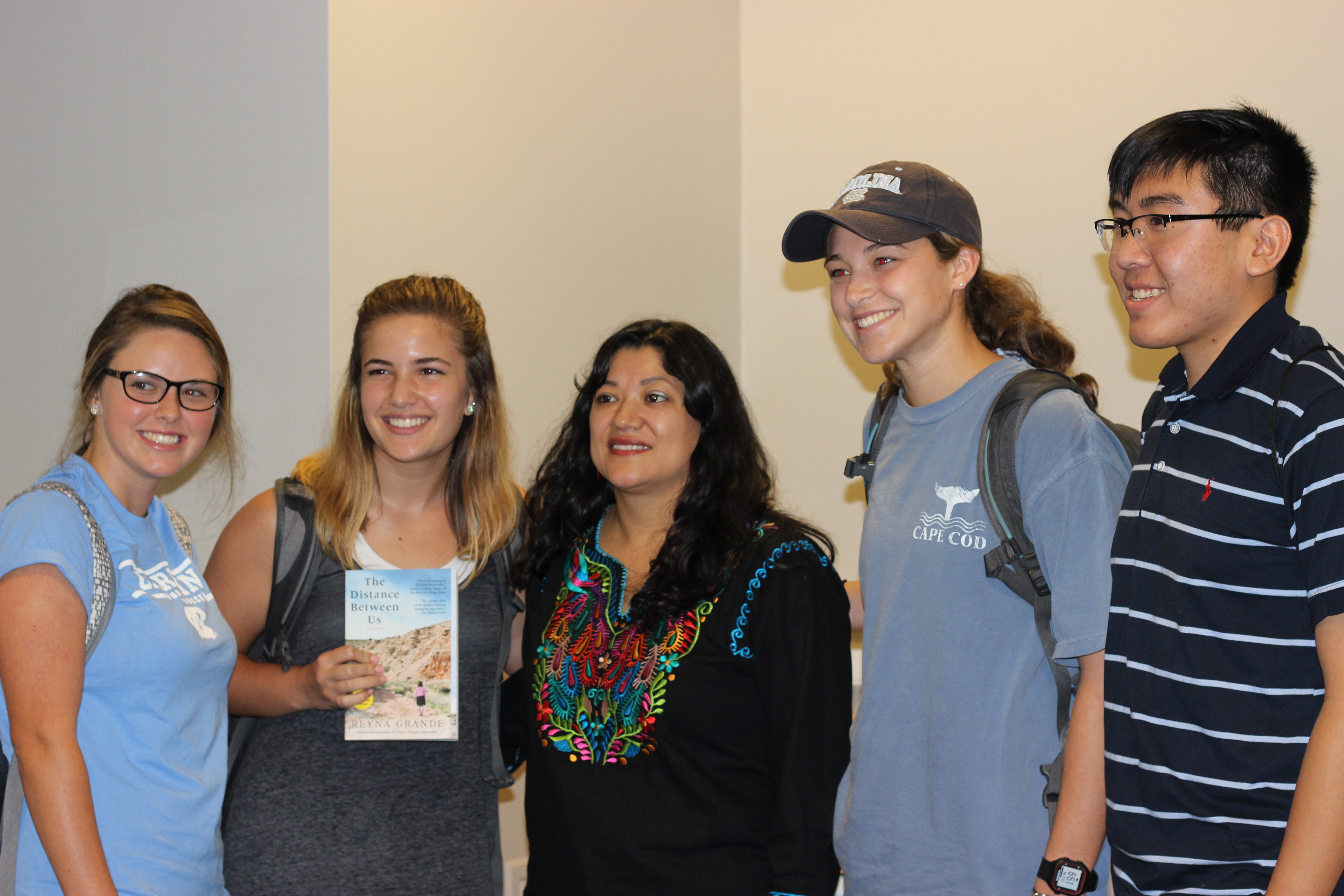 """Reyna Grande posing for a photo with four smiling students, one of whom is holding up a copy of Grande's book """"The Distance Between Us."""""""