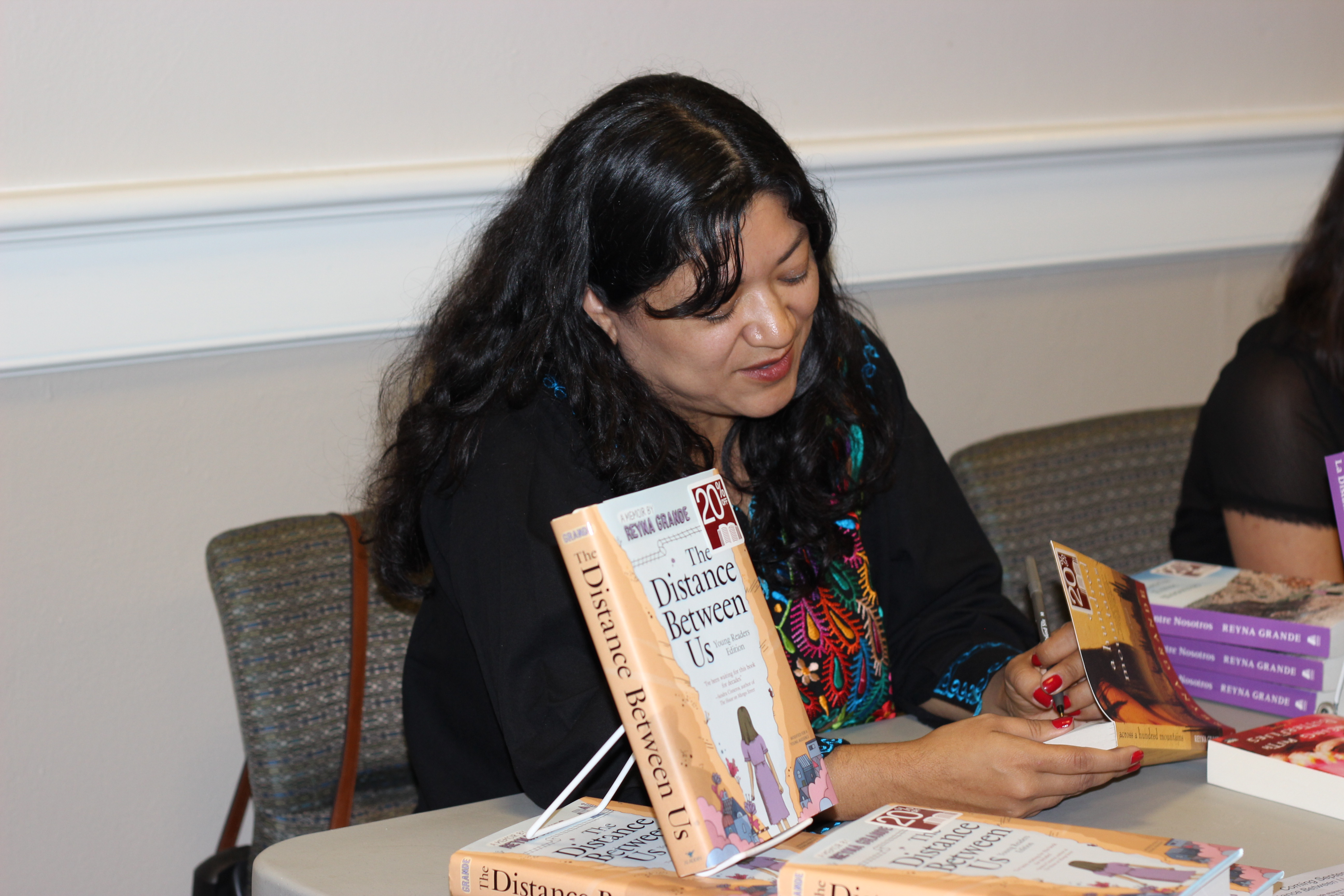 Reyna Grande signing a copy of her book Across A Million Suns as she sits at a large folding table near a display of her book The Distance Between Us.