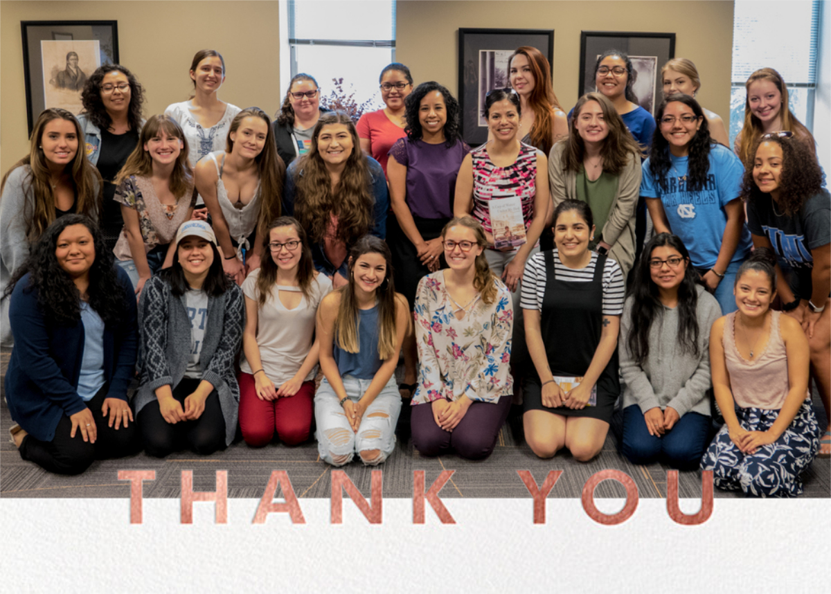 """María Durán and 24 students from her """"Intro to Latina Literature"""" course posing in three tiered rows for a photo with Daisy Hernández, who stands in the center."""