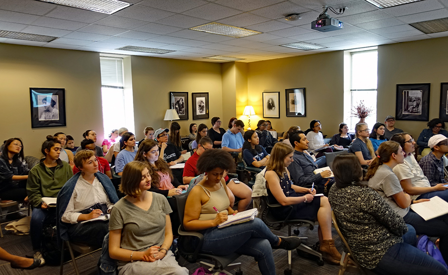Approximately 40 students seated in rows around a large conference room, listening and taking notes as Dr. Paula Moya addresses the crowd (out of frame).