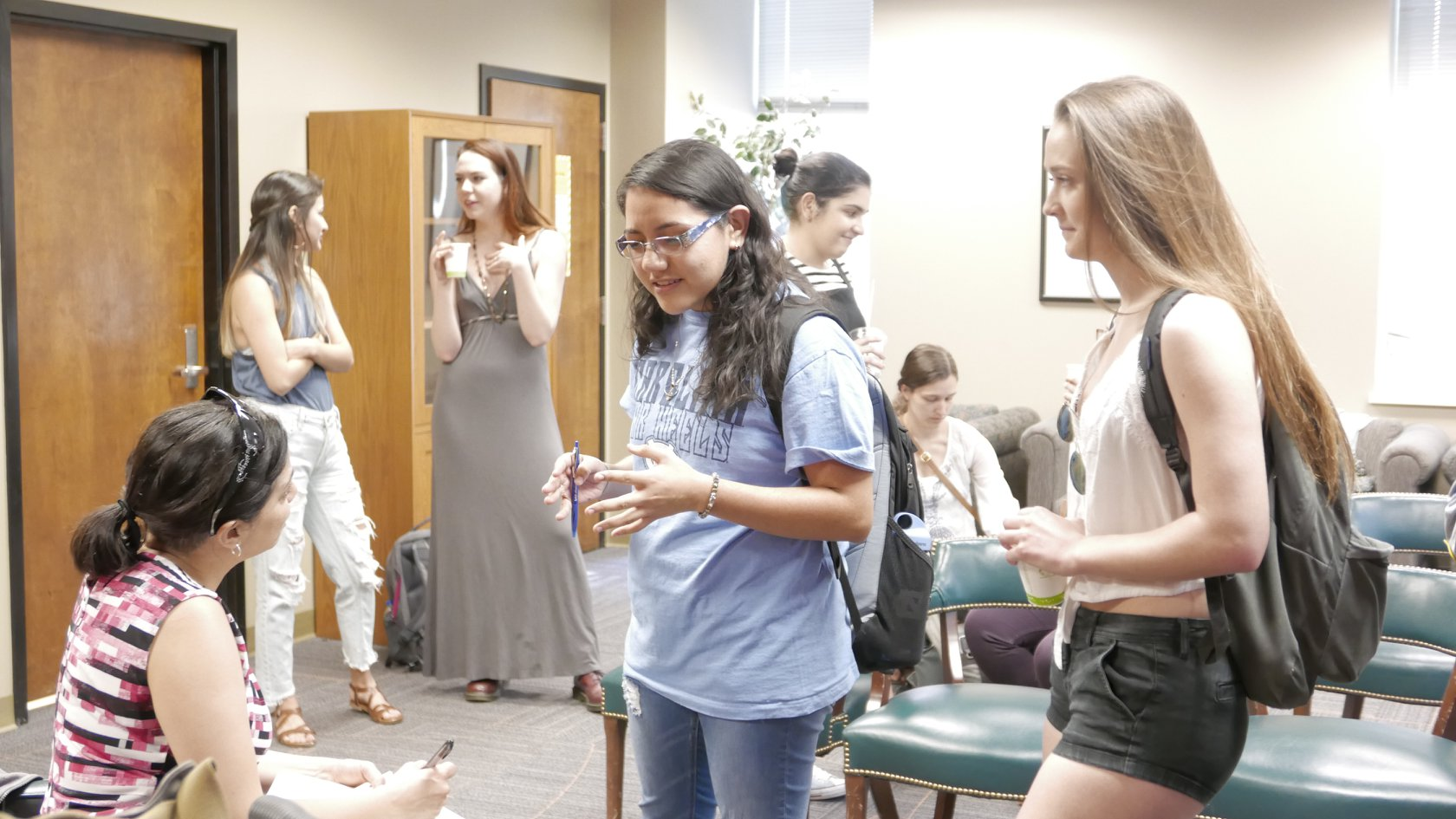 Two students chatting with Daisy Hernández in a large conference room while four other students socialize in the background.