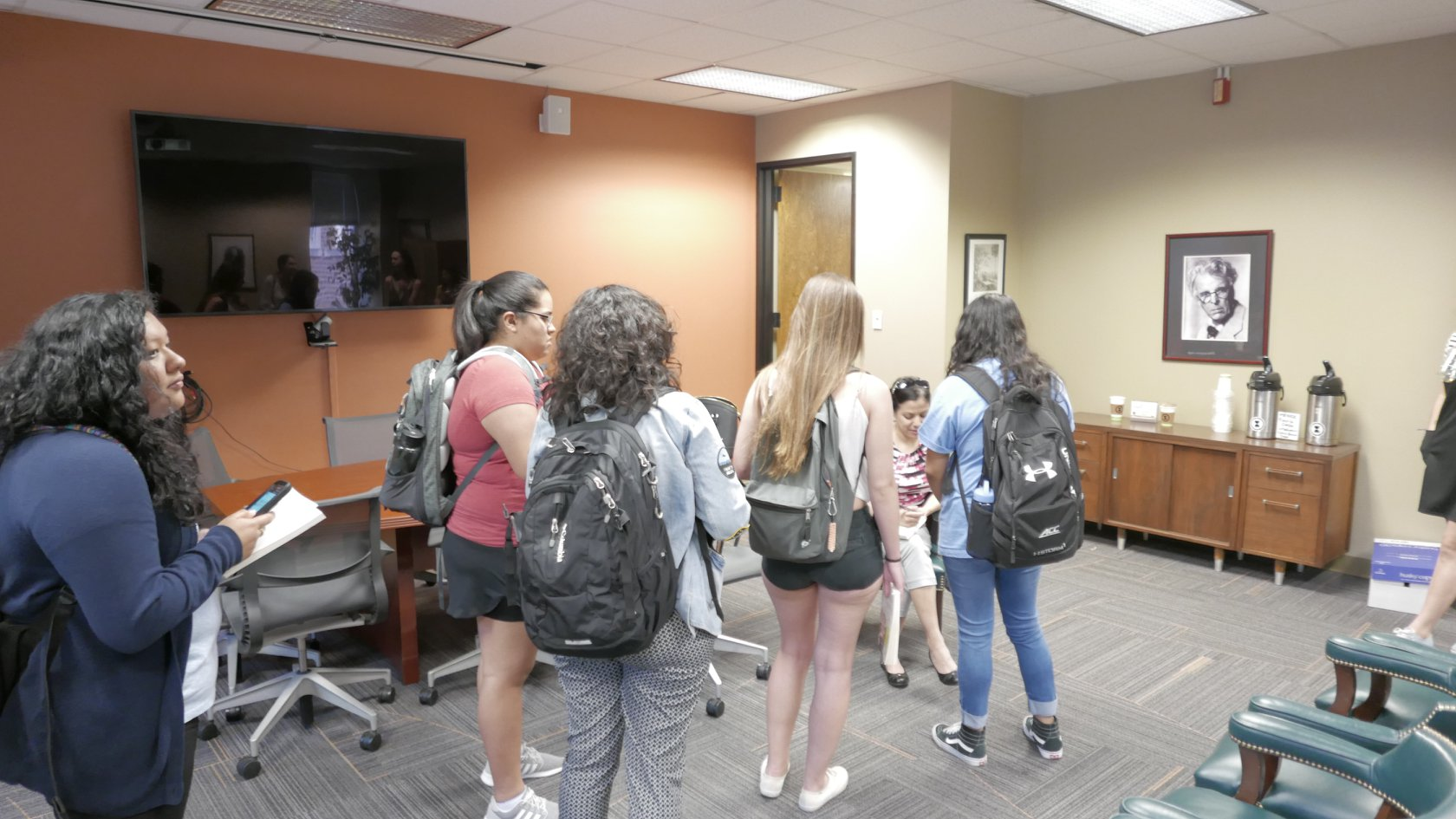 The back of five students as they wait in line to meet with Daisy Hernández, who is seated signing books in the center of a large conference room.