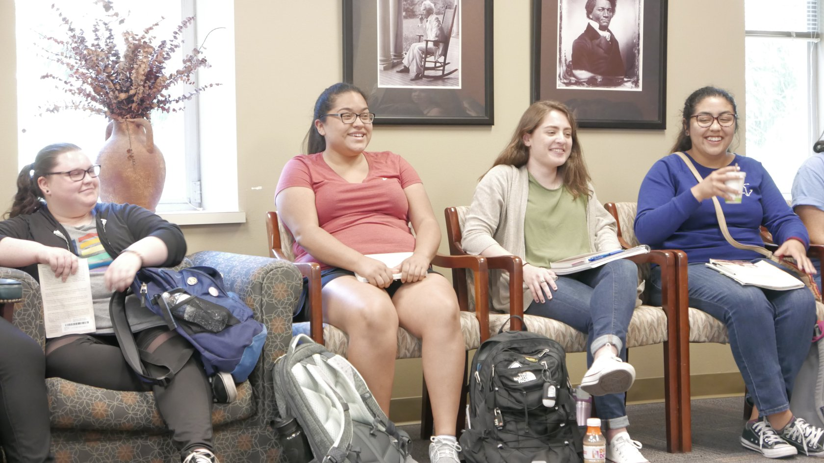Four students seated around the edge of a large conference room, laughing and smiling widely at someone speaking to the group (out of frame).