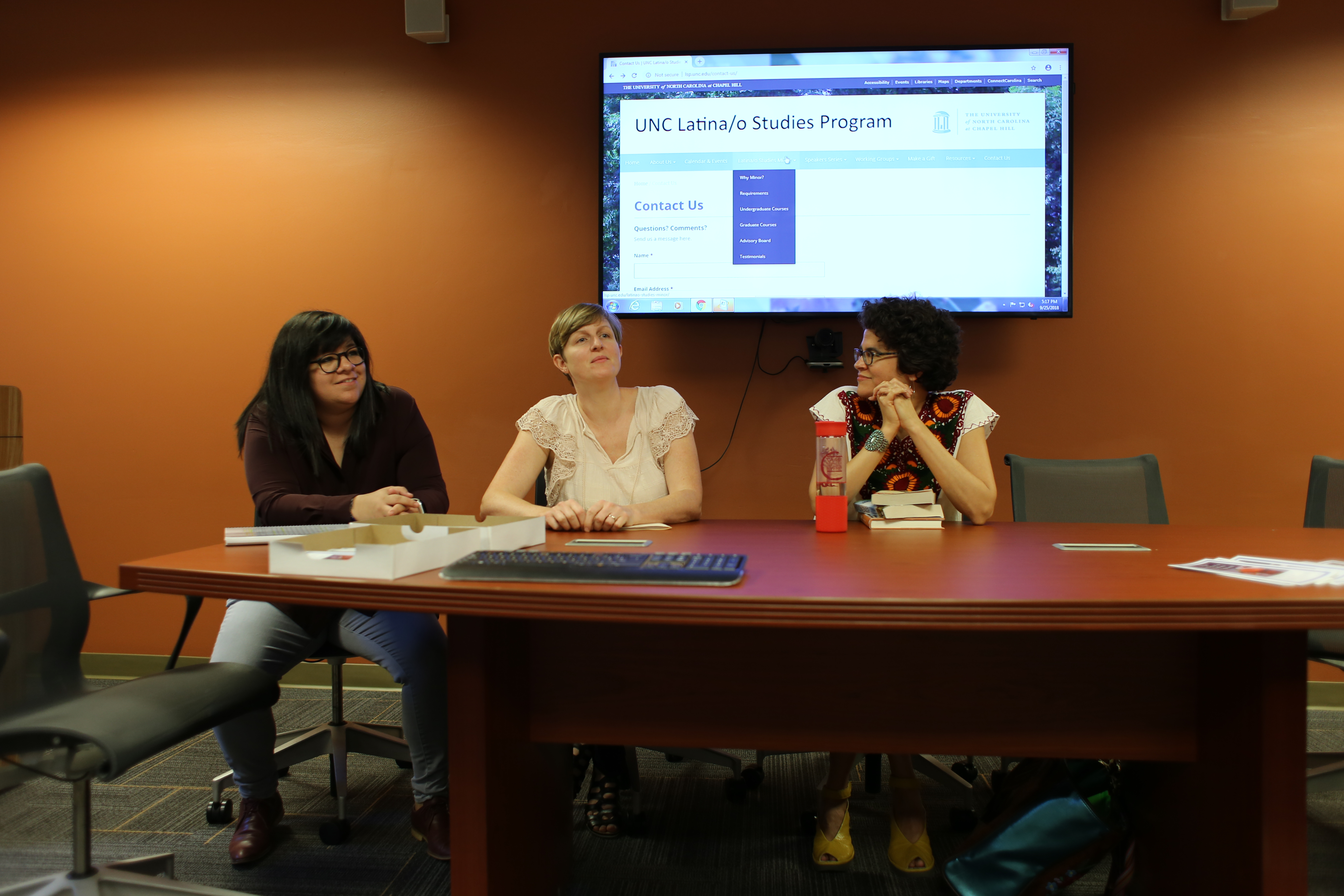 Scholars Alejandra Márquez, Angela Stuesse, and Stephanie Elizondo Griest sitting at a conference table before a projected image of the Latina/o Studies Program website.