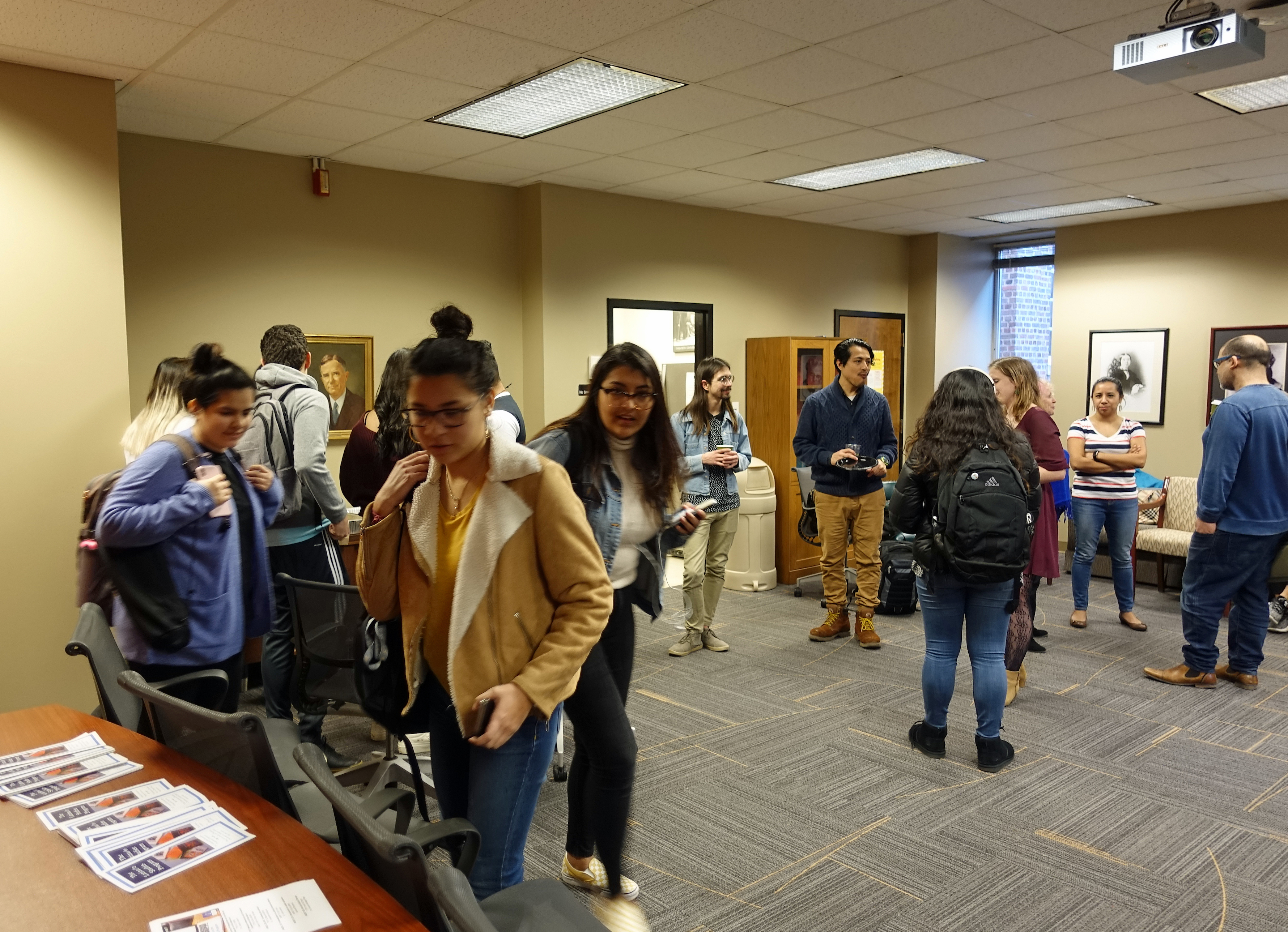 Students gathered in a large conference room and chatting in small groups as one student approaches a table with Latina/o Studies Program pamphlets.