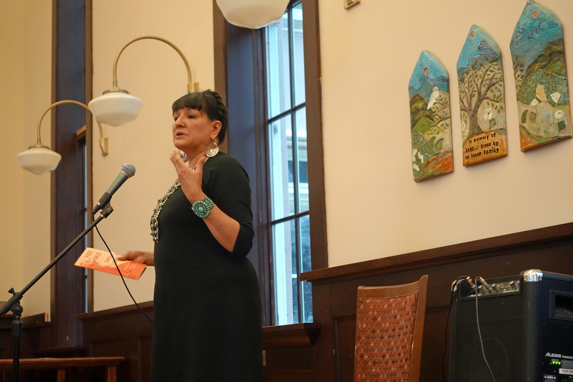 Sandra Cisneros standing at the front of a large event space, gesturing and speaking into a microphone.