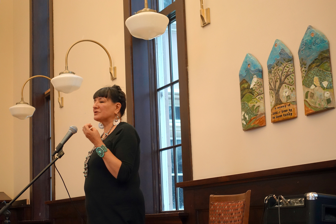 Sandra Cisneros gesturing and speaking into a microphone as she stands at the front of a large event space.