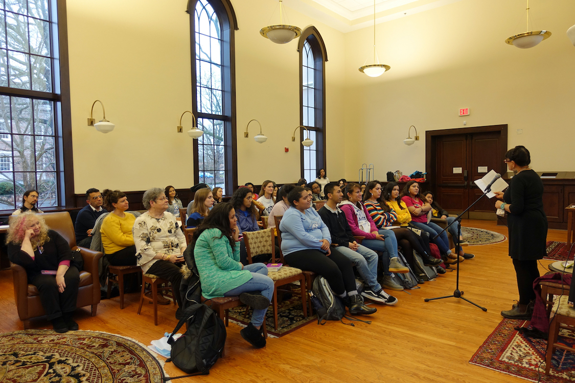 Sandra Cisneros looking out on a crowd of about 50 students and faculty as she speaks into a microphone at the front of a large event space.