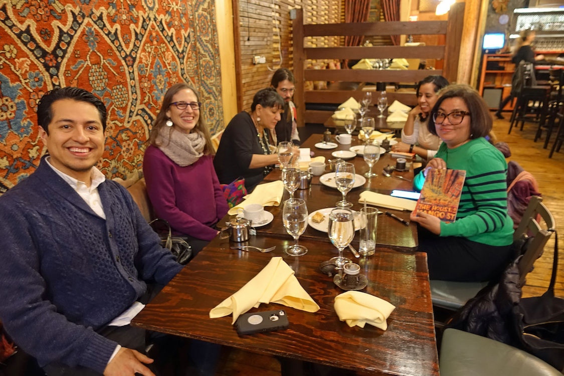 A small group of students and faculty smiling and chatting with Sandra Cisneros as they sit around the table at a post-event dinner.