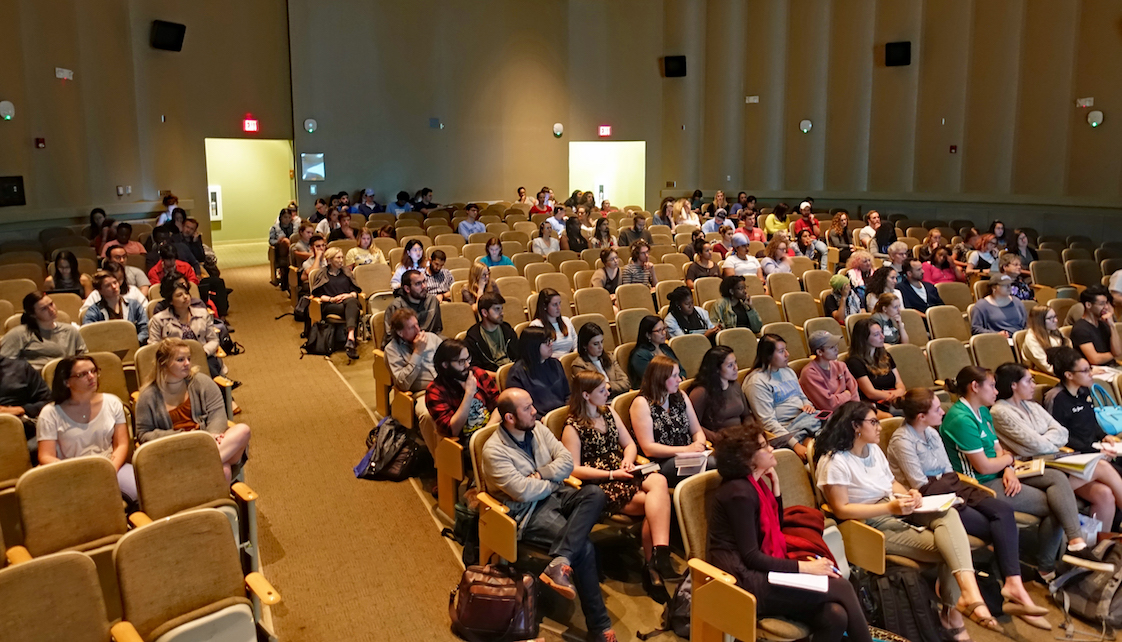 100-120 students and faculty seated in the audience of the Stone Center auditorium listening attentively to someone addressing the crowd (out of frame).