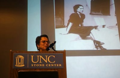 Cherríe Moraga standing at a podium and speaking into a microphone before a large projected photo of her mother as a young woman.