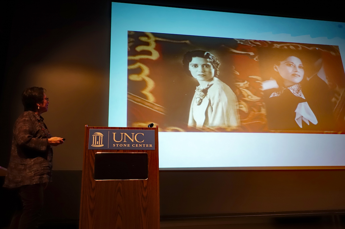 Cherríe Moraga standing to the left of a podium and gesturing at a projected slide from her presentation.