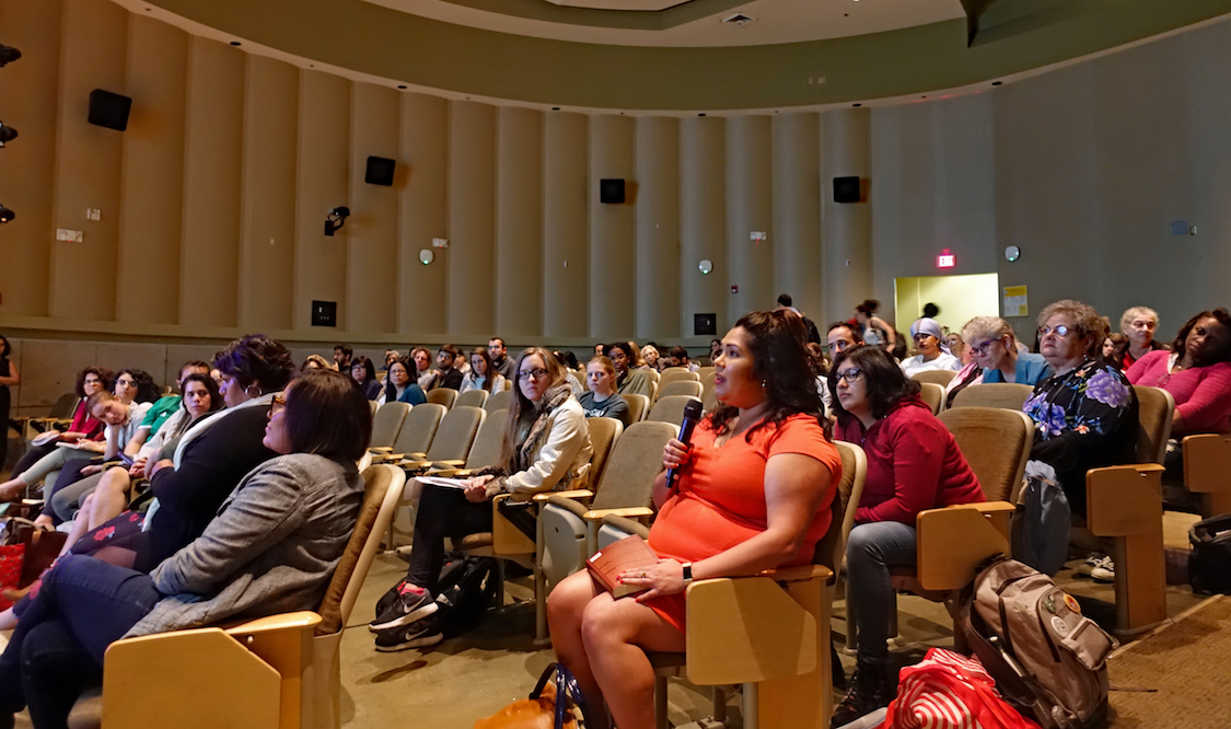 About 60 students and faculty seated in the audience of the Stone Center auditorium during a Q&A with visiting speaker Cherríe Moraga, watching one student ask a question into a microphone.