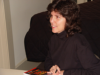 Achy Obejas signs a book while speaking to an audience member