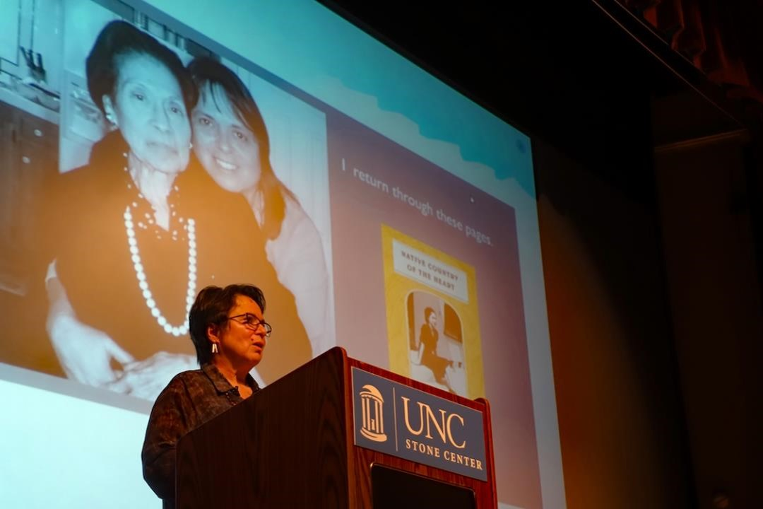Cherríe Moraga standing at a podium and speaking into a microphone before a large projected photo of her mother as a young woman