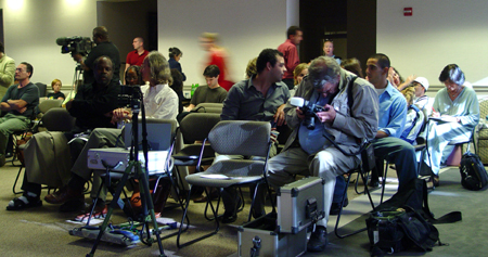 A man sits preparing his camera to record while audience members prepare to take their seats