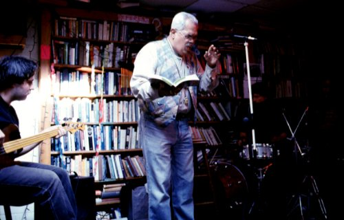Miguel Algarín reads at the Skylight Exchange with a book in hand, accompanied by a guitarist and drummer