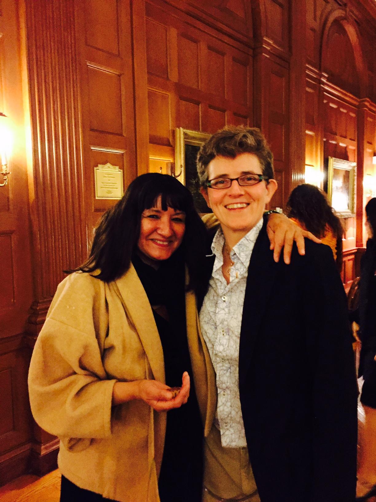 Sandra Cisneros wraps her arm around LSP Director M. DeGuzmán as the two smile towards the camera