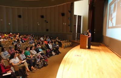 Latina/o Studies Program graduate assistant María Durán standing at a podium at the front of the Stone Center auditorium and introducing Cherríe Moraga.