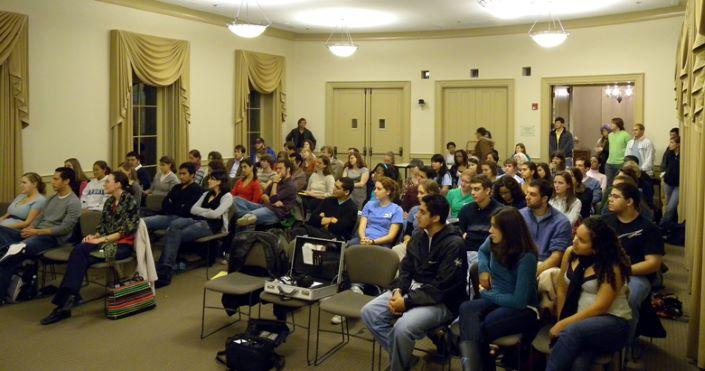 Audience of faculty, students, and community members sit in rows, listening to Cristia Henríquez speak in The University Room of Hyde Hall, IAH. November 13, 2008.