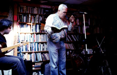 Miguel Algarín reads at The Skylight Exchange, Chapel Hill, with a book in hand accompanied by musicians. March 26, 2000.